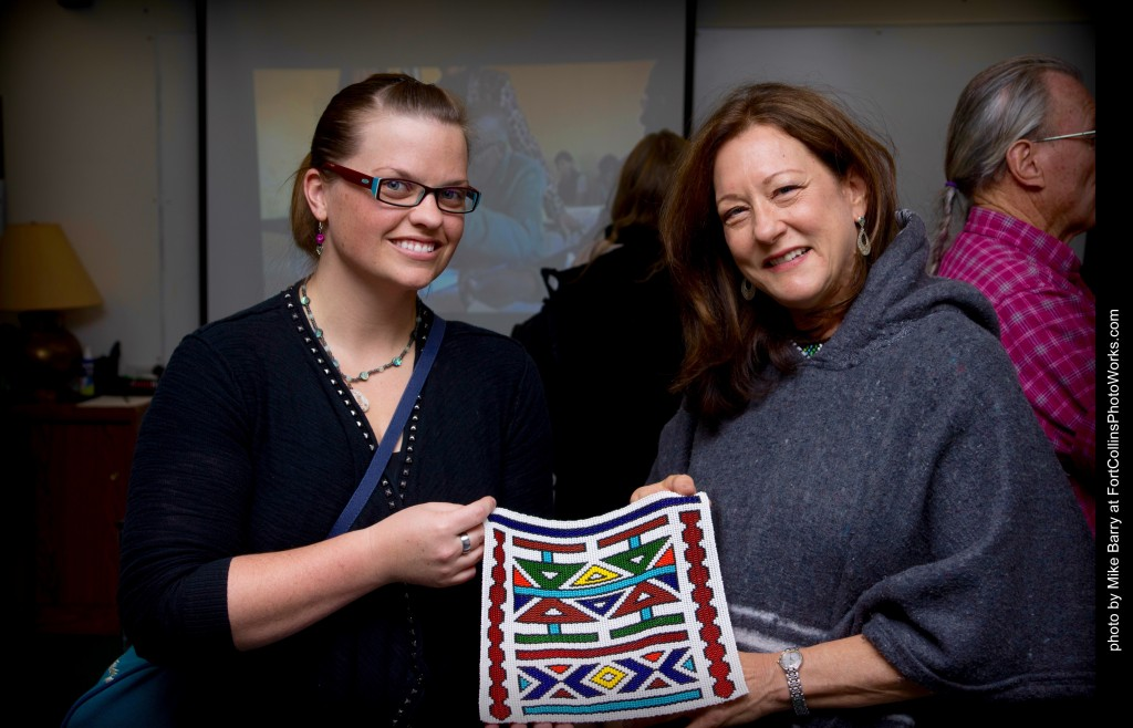 DeVereaux and a trip participant showcase a piece of art during an local art exhibit organized by trip participants in the fall. Photo by Mike Barry.