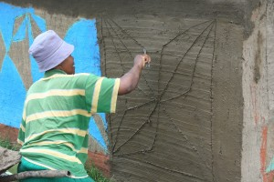 Elizabeth Twala completing a ditema house mural. Photo by David Riep