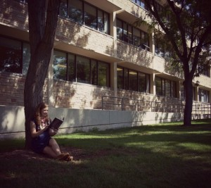 English department Communications Intern Ashley Alfirevic reads under a tree on the southside of Eddy Hall.
