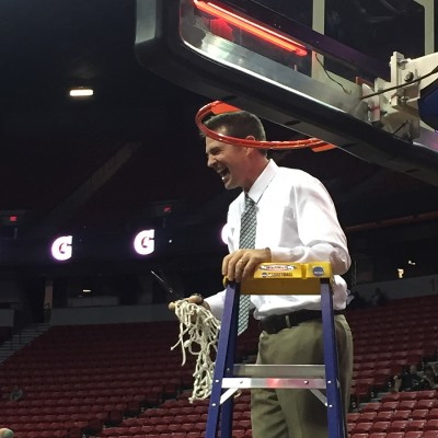 Coach Ryun Williams cuts down the net.