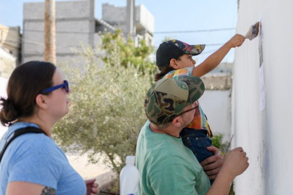 Faris helps Vince and Chelsea glue the first poster of the international art exchange to the wall outside the community center in Jerash refugee camp Jordan.