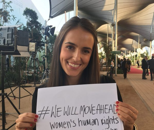 Vélez holding a side that has #WEWILLMOVEAHEAD women's human rights written on it