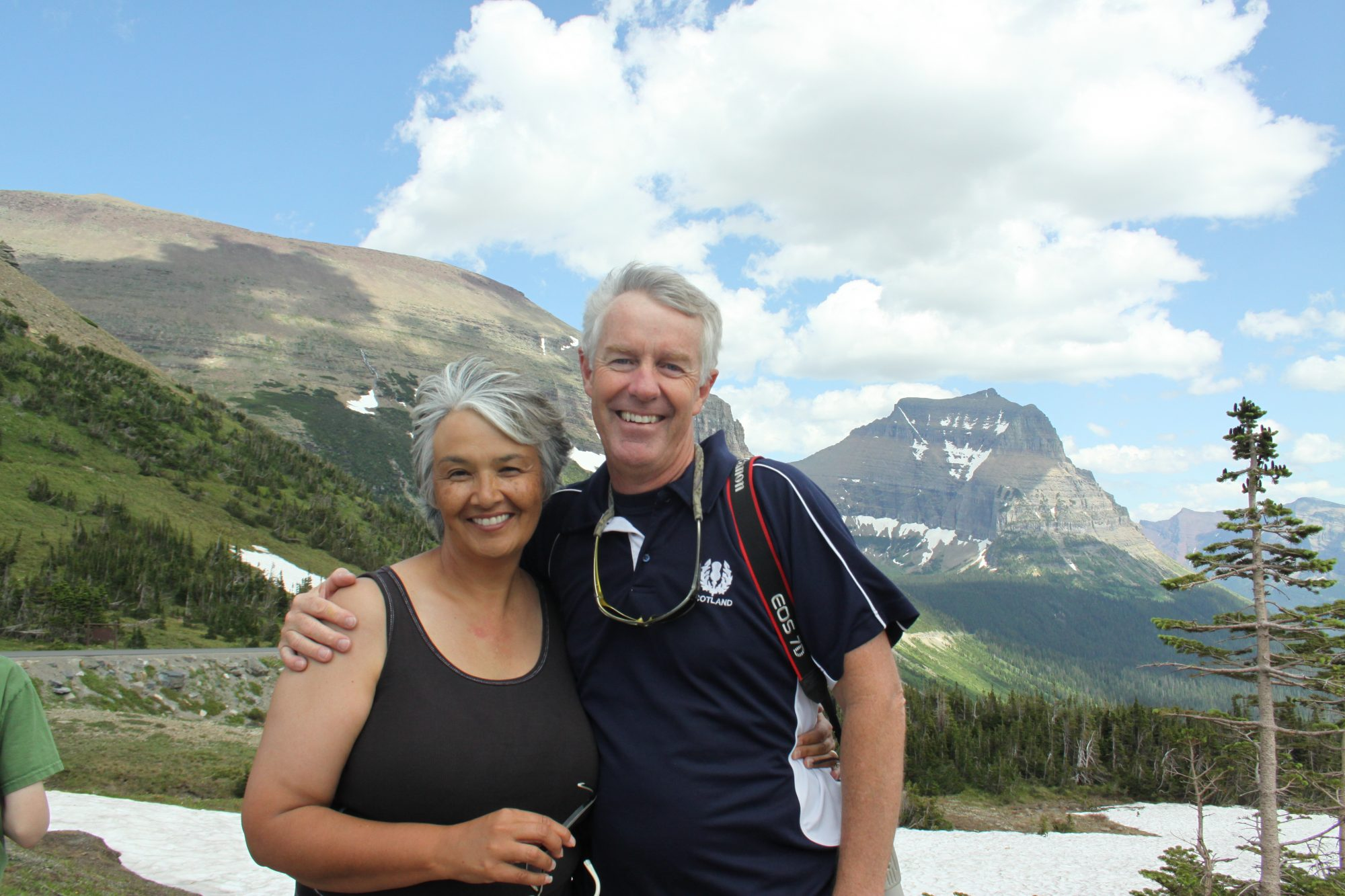 Susan Harness and her husband Rick smile in front of a mountain range