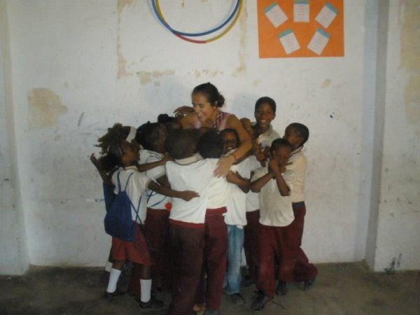 Vélez getting hugged by half a dozen school children in Colombia