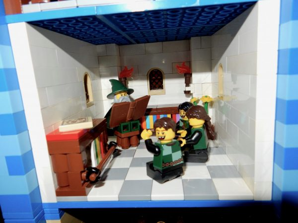 Three Lego knights reading while a wizard acts as a teacher