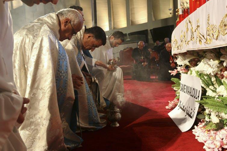 Maronites kneel in prayer