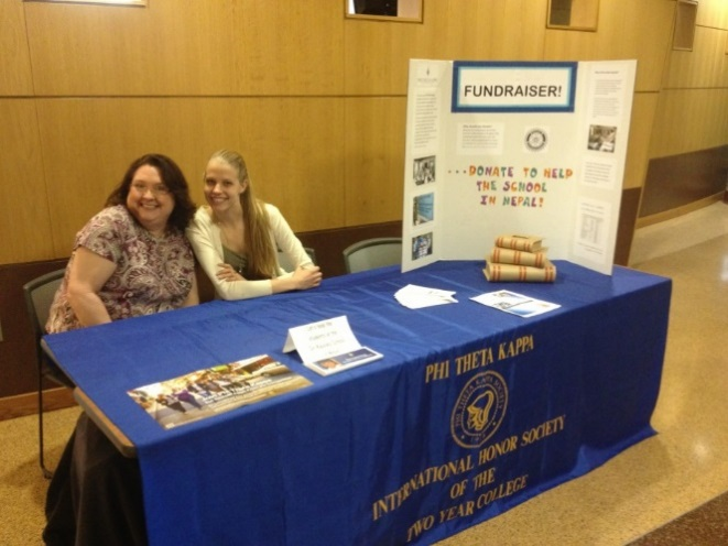 Two people sitting at a fundraising table at Front Range Community College