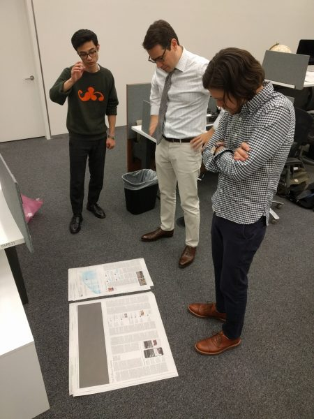 Gabriel Dance consulting with other employees at the New York Times about layout