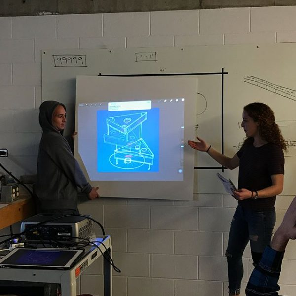 Students presenting their workshop design using digital projector