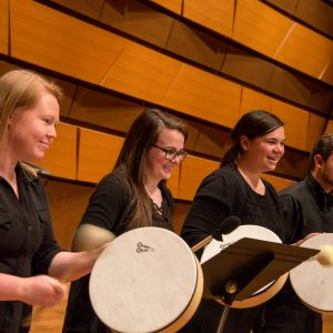 Students smile while playing percussion instruments