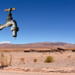 A faucet drips in front of an arid landscape