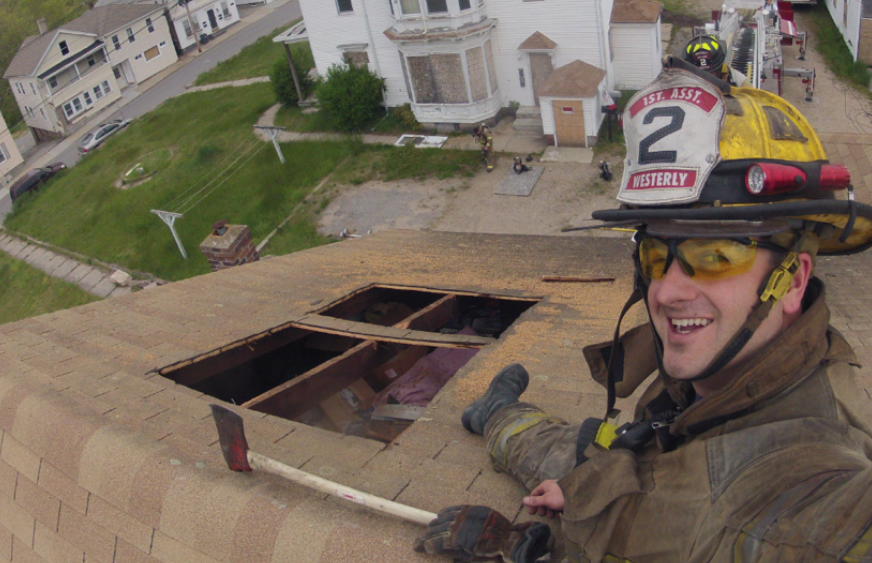 Tim Amidon on the roof of a house as part of the Westerly Fire Department
