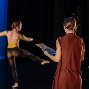 Dancer practices while teacher takes notes on form