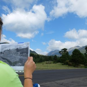 Student holds up a historical photography in front of the same present day location in Rocky Mountain National Park