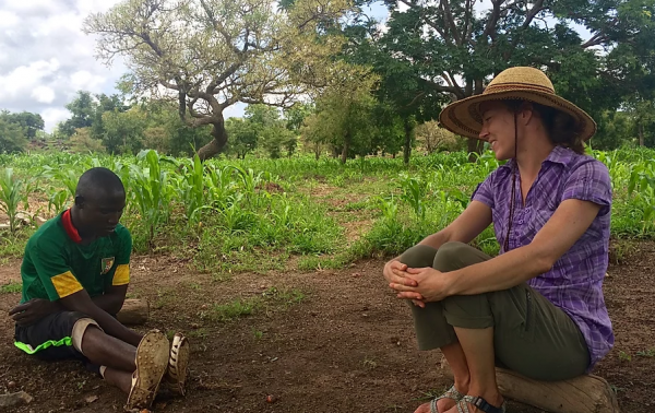 Jessie Luna sitting and talking to a Burkinabe man
