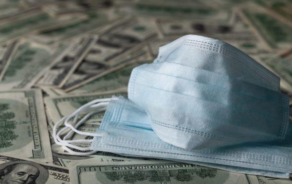 Medical face mask and dollar banknotes
