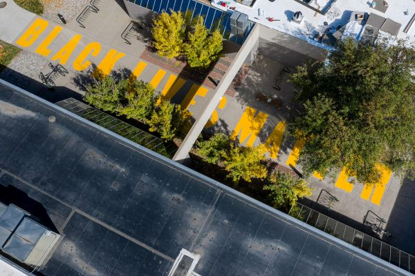 """Faculty and students in a collaborative between Art, Ethnic Studies, and the Black/African American Culture Center, paint """"Black Lives Matter"""" on the sidewalk outside the Art Building, October 12, 2020"""