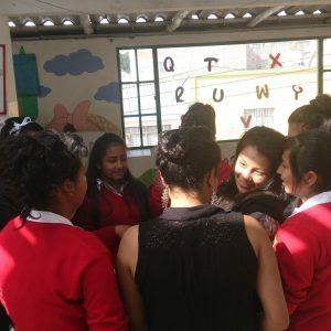 Students gather in a circle inside a classroom in Colombia