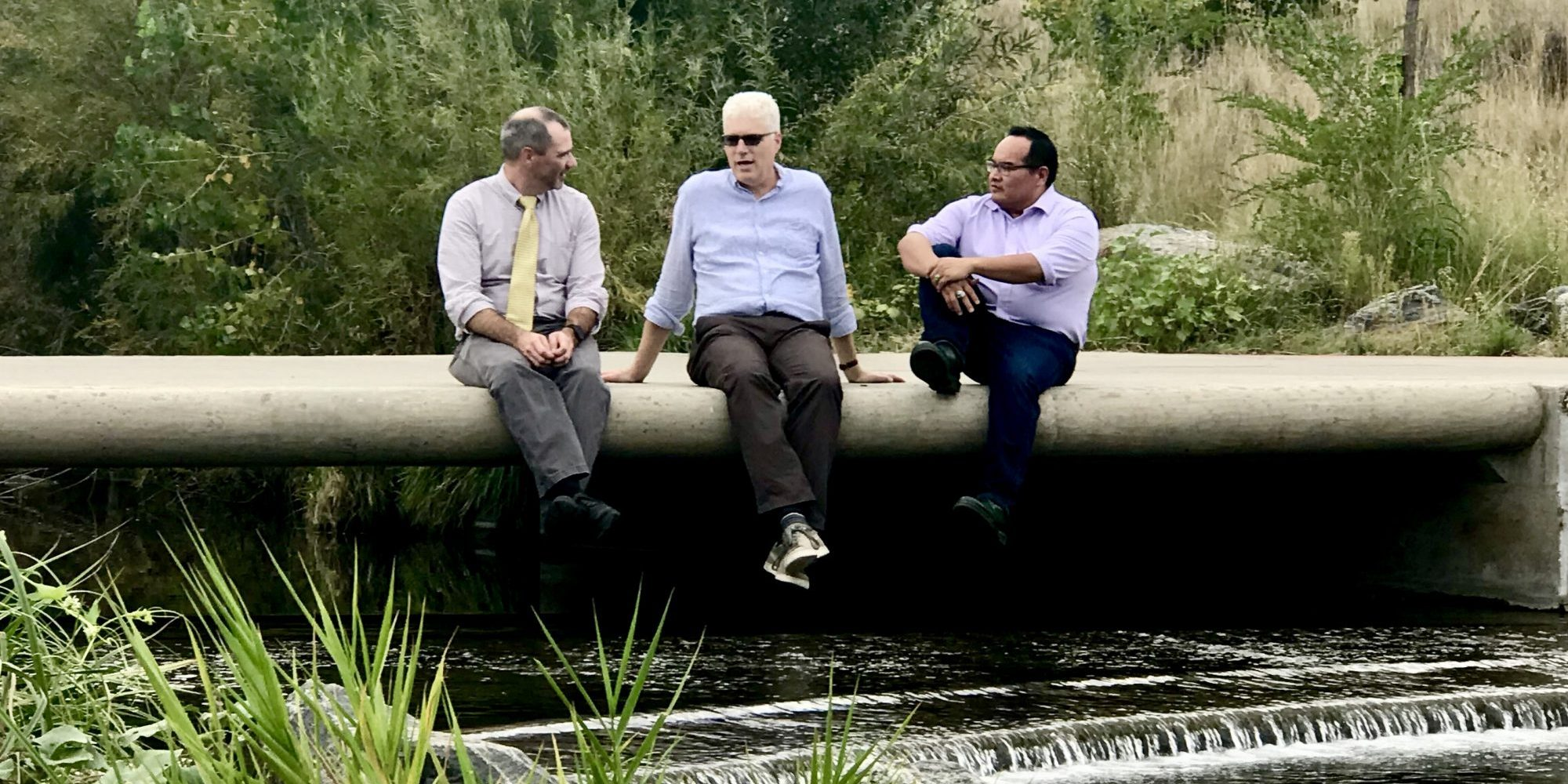 Conner, Dickinson, and Aoki chat with their legs dangling over the Platte River